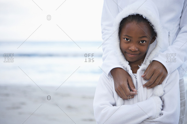 Mother and daughter  in white clothing standing on beach, smiling, front view, portrait
