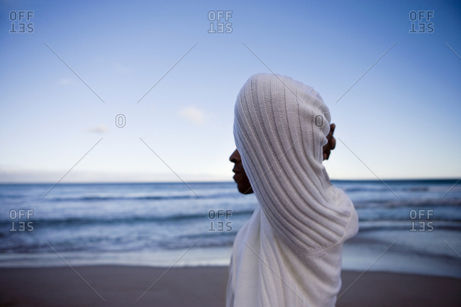 Man in white top standing on beach at sunset, , face obscured, profile