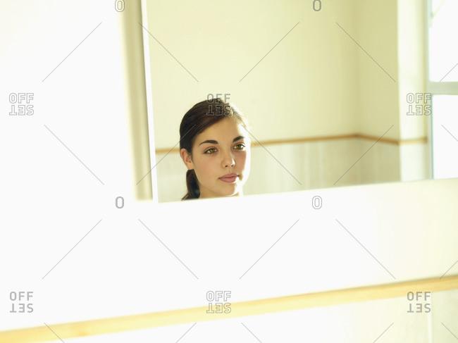 Teenage girl looking at reflection in bathroom mirror, smiling, headshot