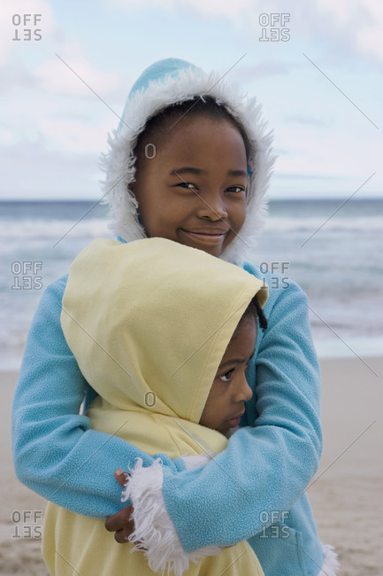 Two girls wearing fleeces with hoods, embracing on beach, close-up, smiling, portrait