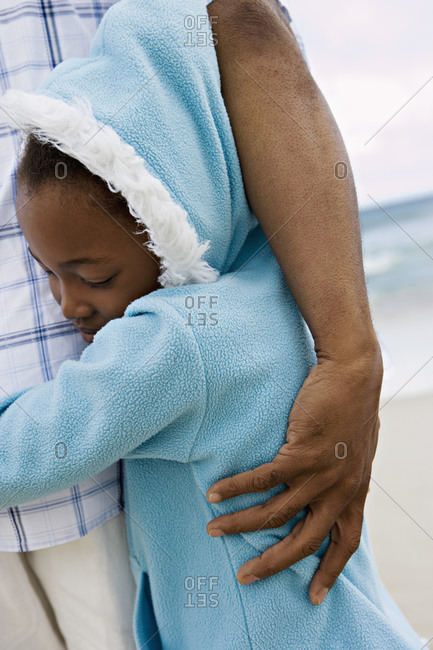 Girl  in blue fleece with hood embracing father on beach, smiling, eyes closed, close-up