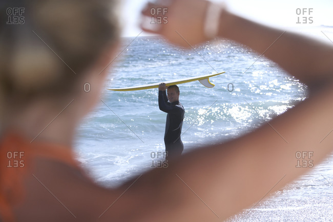 Young woman watching surfer standing in sea, rear view, focus on man in background