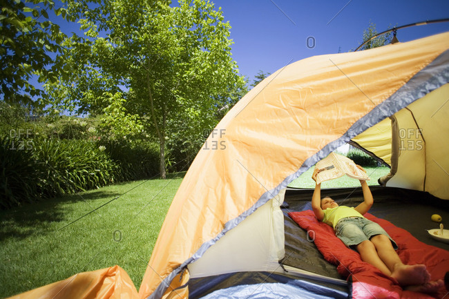 Girl lying on red sleeping bag inside orange tent on garden lawn, reading book