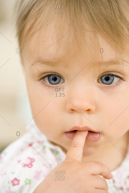 Baby girl with finger in mouth, close-up