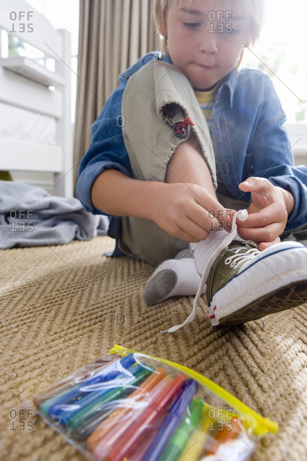 Boy tying shoelace in bedroom, low angle view