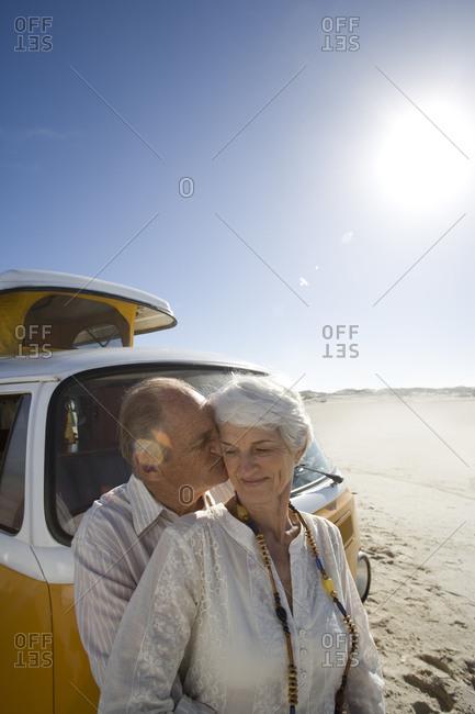 Senior couple on beach by camper van, man kissing woman on cheek, close-up