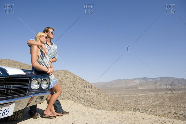 Young couple arm in arm leaning on car in desert looking at view, low angle view