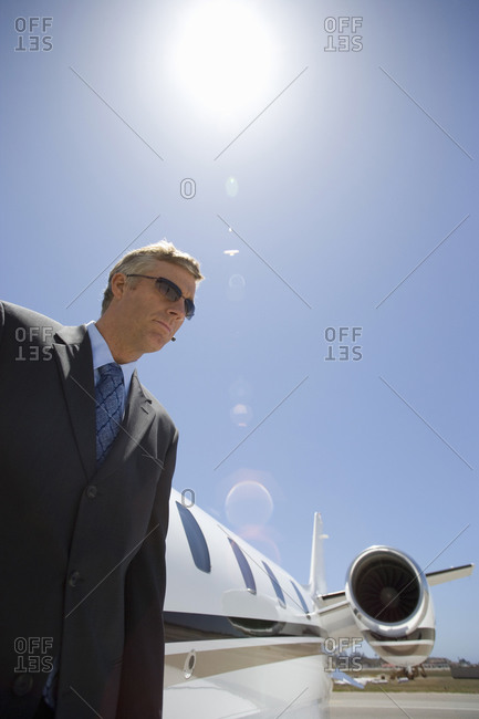 Businessman by aeroplane on runway, low angle view