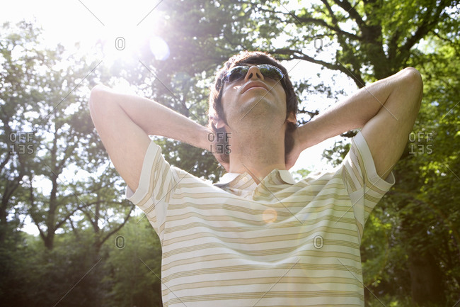 20's man relaxing with sunglasses in leafy countryside looking up at sky,