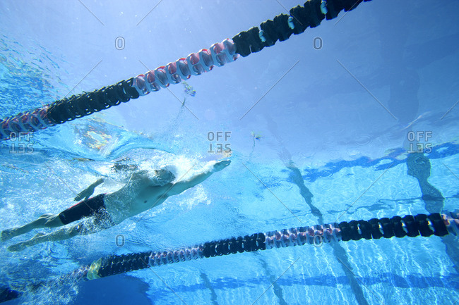 Man swimming lengths in swimming pool, underwater view