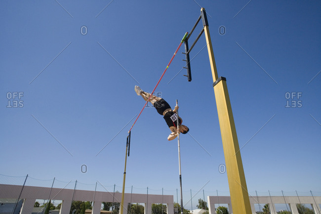 Male pole vault athlete going over bar, low angle view