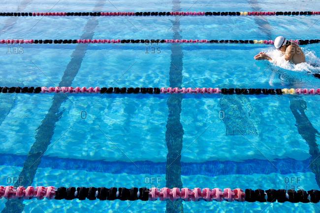 Young man swimming in lane in swimming pool