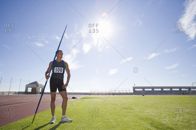 Male athlete with pole, low angle view (lens flare)