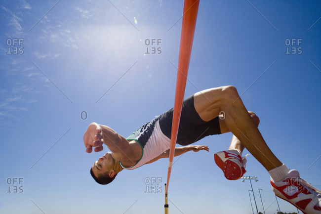 Young male athlete jumping over bar, low angle view
