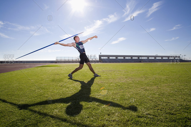 Male athlete preparing to throw javelin, low angle view (lens flare)