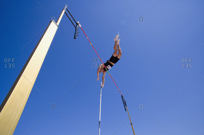 Pole vault athlete going over bar, low angle view