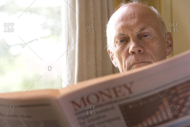 Senior man reading newspaper, close-up