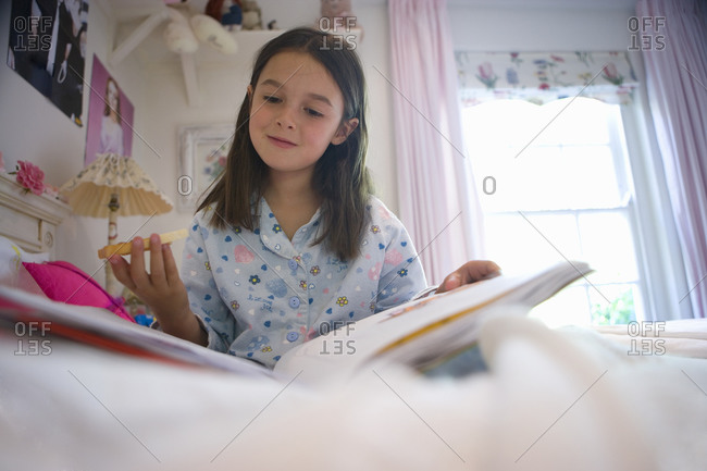Girl  in pajamas reading in bed, low angle view