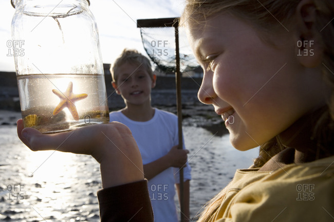 Girl  holding up jar containing starfish by boy