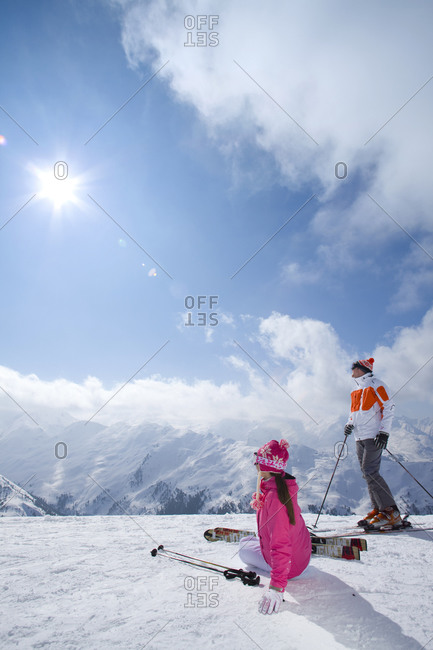 Skiers sitting in snow looking at mountains