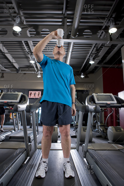 Man drinking from water bottle on treadmill in health club