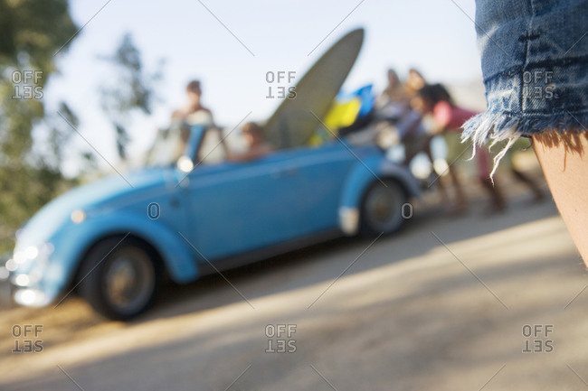 Teenager looking at friends beside blue car and surfboard, rear view, focus on foreground (tilt)
