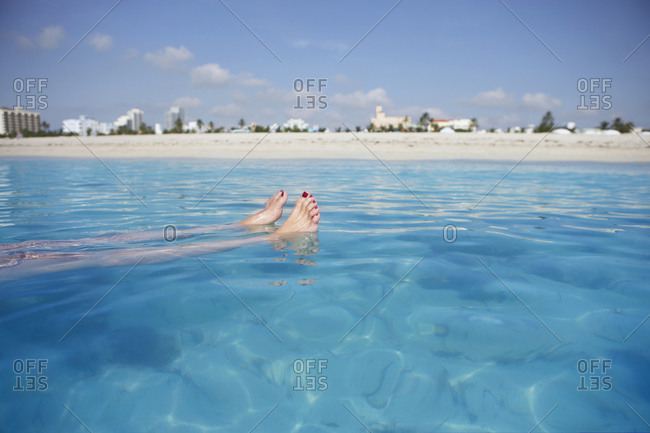 South Africa, Cape Town, woman floating in sea, low section, beach in background, surface level