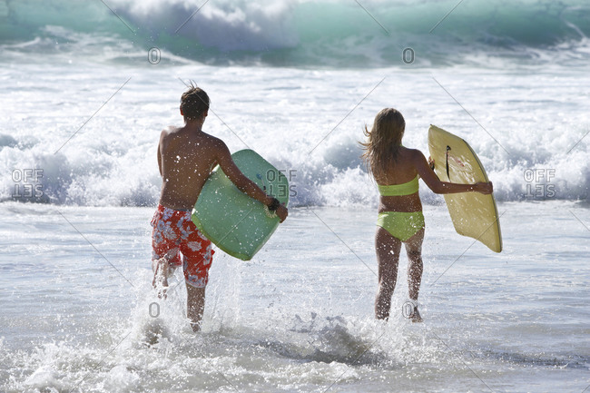 Two teenage (13-15) bodysurfers running into surf, carrying bodyboards, side by side, rear view
