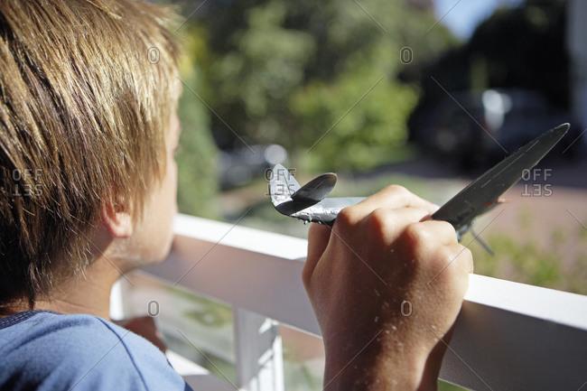 Boy (7-9) standing on veranda, holding toy aeroplane, close-up, rear view