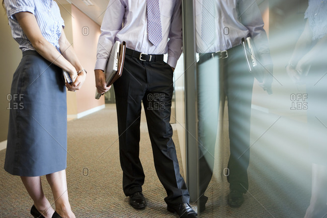 Businessman and businesswoman talking in corridor beside office window, low section, side view