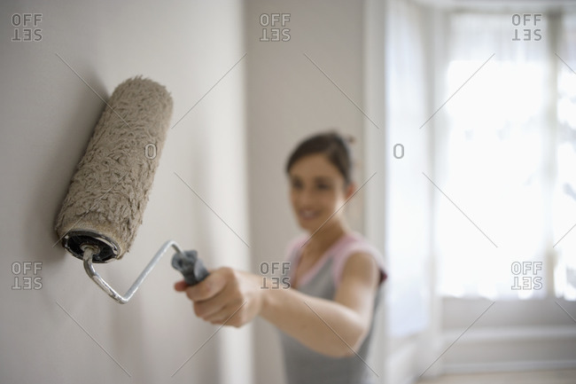 Woman decorating at home, painting wall with paint roller, smiling, side view