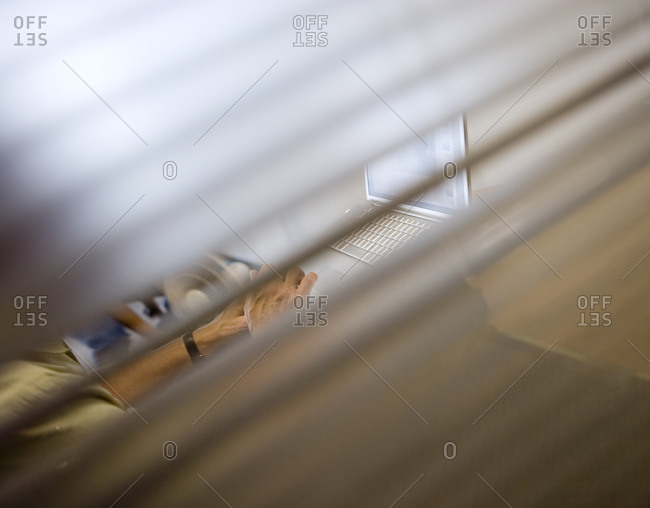 View through office window of businessman using laptop, side view, focus on background (tilt)