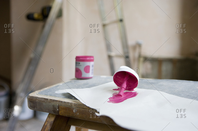 Small tin of pink paint and paintbrush on paper in undecorated room, close-up, focus on foreground