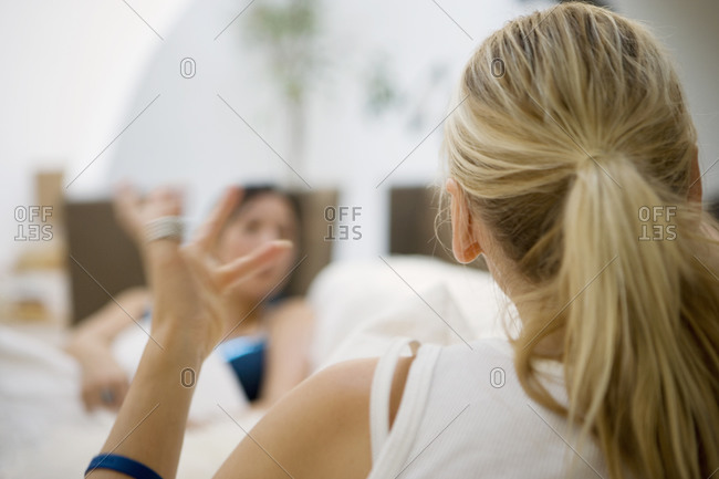 Blonde woman talking to friend at home, making hand gesture, rear view, focus on foreground
