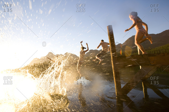 Couple and daughter (8-10) jumping off jetty, low angle view (lens flare)