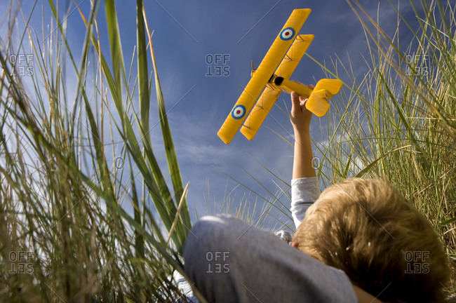 Boy (7-9 years) holding up toy airplane whilst lying on long grass, low angle view