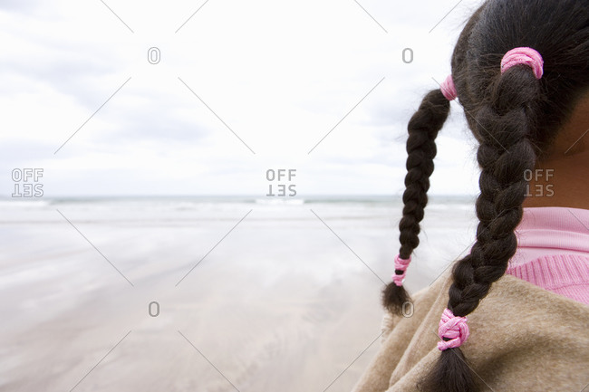 Girl (7-9) on beach, side view (section)