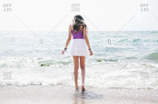 Rear view of little girl walking into water