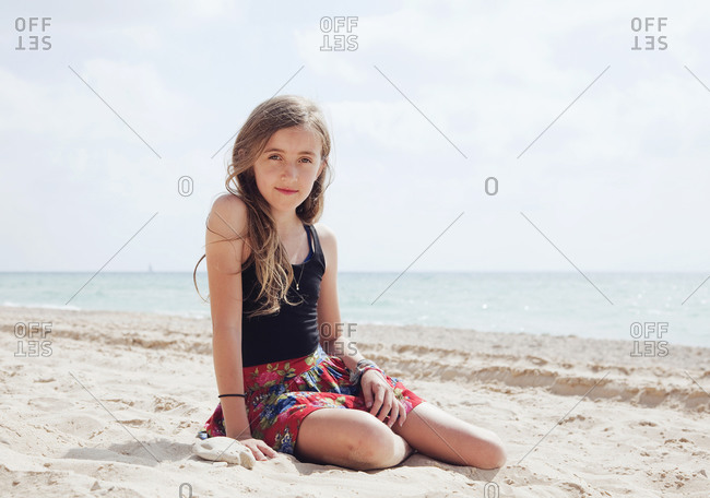 Portrait of young girl sitting at beach