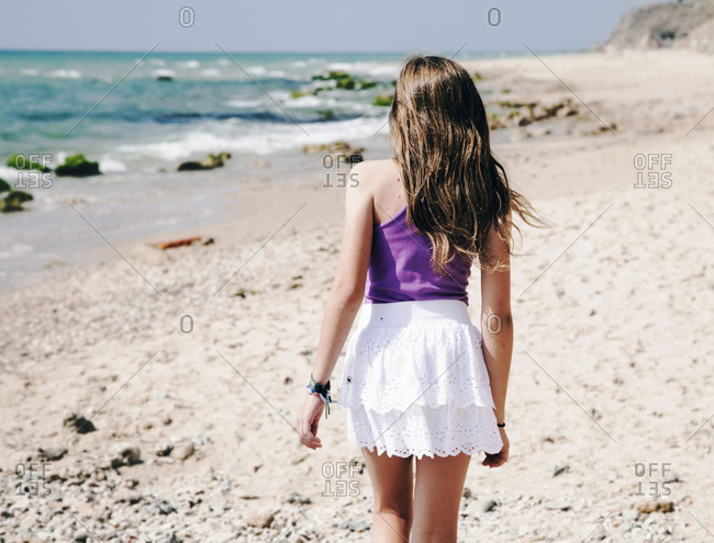 Rear view of young girl walking at beach