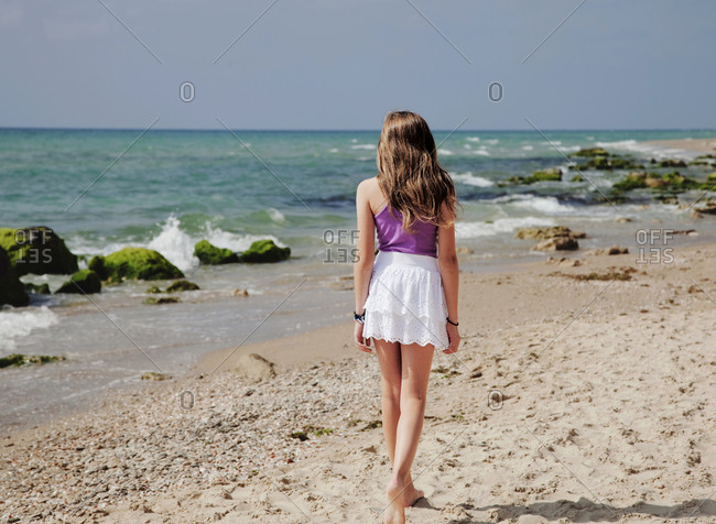 Rear view of little girl walking at beach