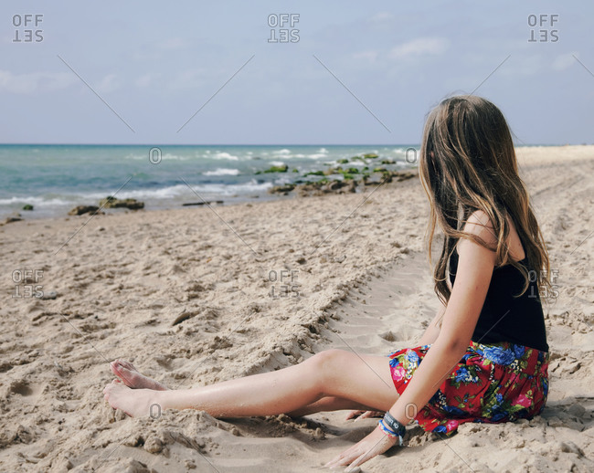 Young girl sitting at the beach