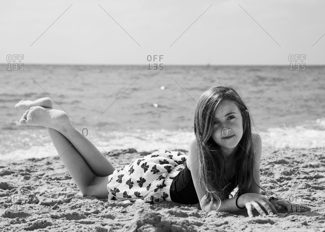 Portrait of young girl lying at the beach