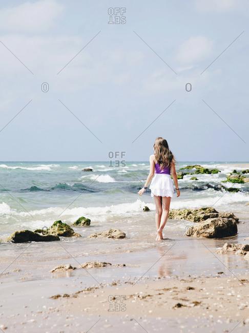 Rear view of young girl walking at seashore