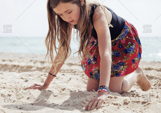 Portrait of young girl playing in the sand