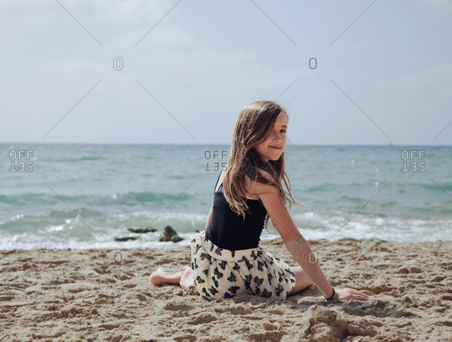 Portrait of girl sitting in sand