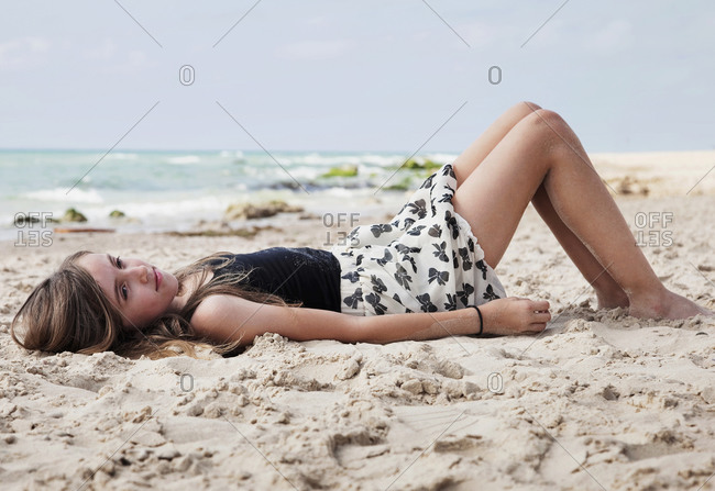 Portrait of young girl lying in the sand