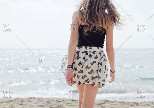 Rear view of girl walking at the beach