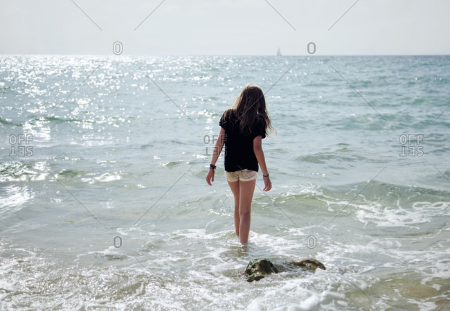 Rear view of young girl walking in shallow water