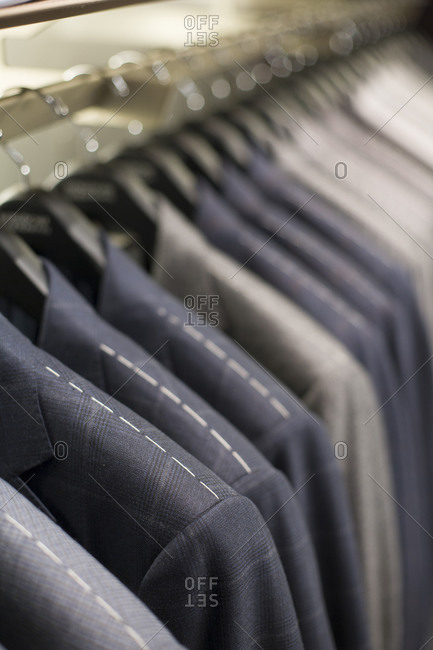Close up of suit jackets hanging in a row
